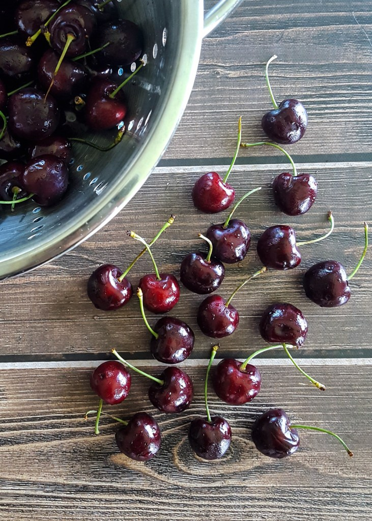 A pile of fresh sweet cherries spread over a wooden surface.   FeastInThyme.com
