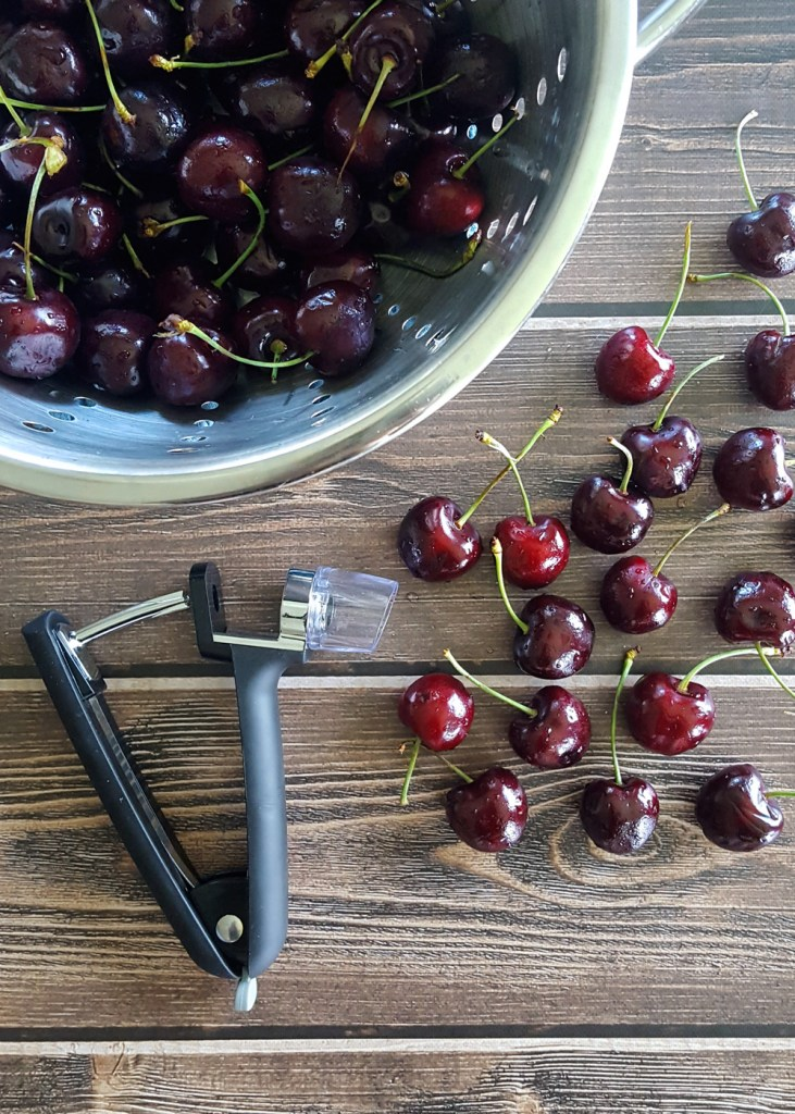 Piles of fresh red sweet cherries alongside a cherry pitter. | FeastInThyme.com
