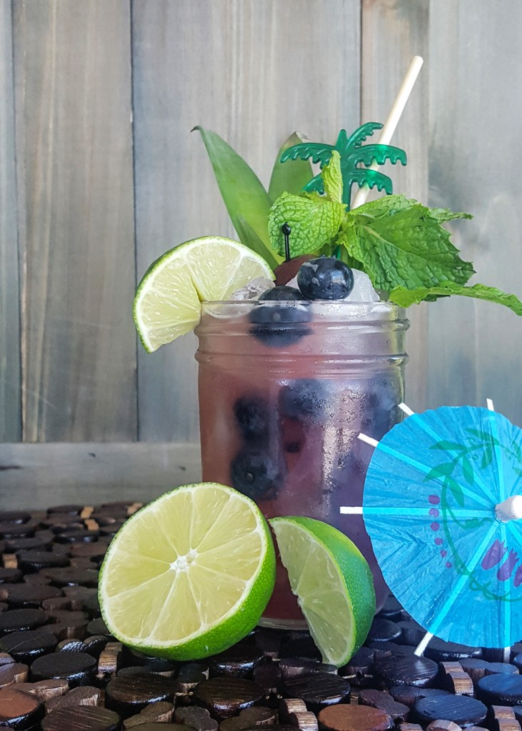 A fully garnished blueberry rum tiki cocktail | FeastInThyme.com