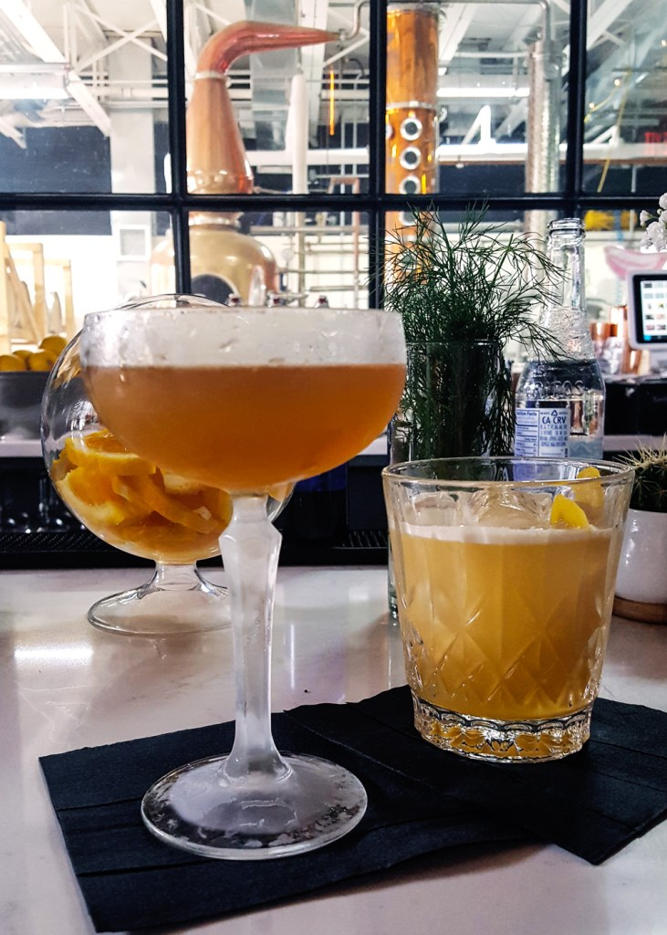 Two cocktails, with a view of the distillery and copper still behind them at Asbury Park Distilling Co. | A Review from FeastInThyme.com