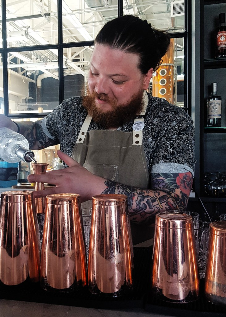 One of the bartenders (Dan) mixing a drink behind the bar at Asbury Park Distilling Co. | A Review from FeastInThyme.com