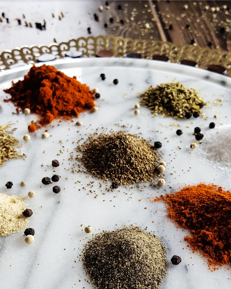 Piles of individual spices and dried herbs on a marble platter. | FeastInThyme.com