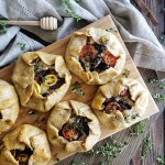 A hearty cornmeal crust wraps up layers of #summer flavor in these rustic Ratatouille Hand Pies. Stacked roasted #eggplant, ripe heirloom #tomato, melty #cheese, and a sprinkling of fresh herbs and briny# olives makes for a travel-ready meal, perfect for any #picnic or #potuck. #handpies #gallette #travel | FeastInThyme.com