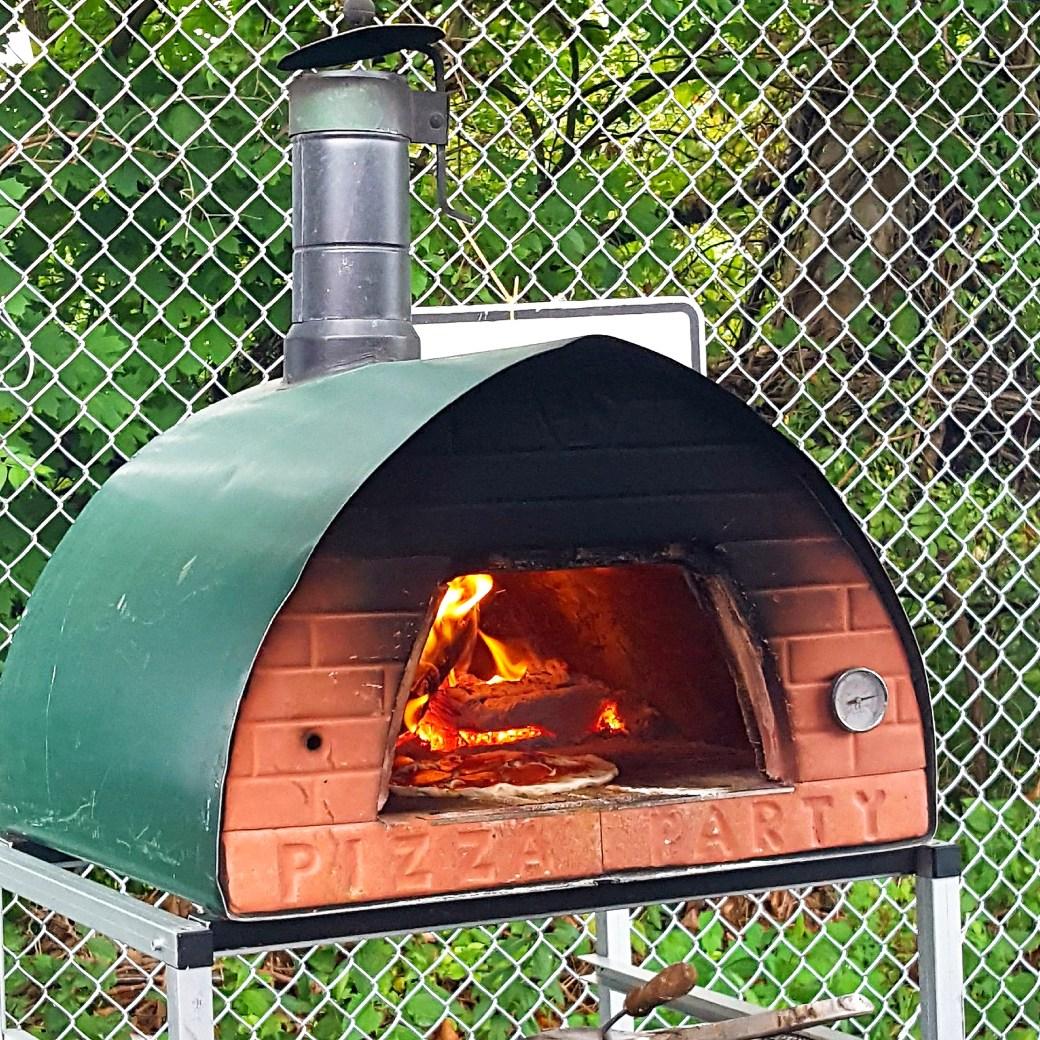 Pizza Nocciano's mobile brick fire pizza oven in action.