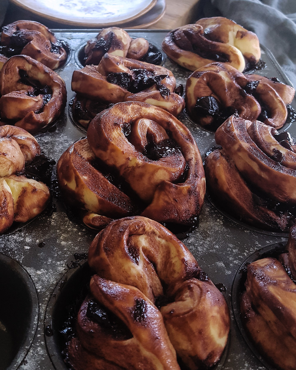 A close up of a tray of baked Cherry Chocolate Babka Pull Apart Muffins.