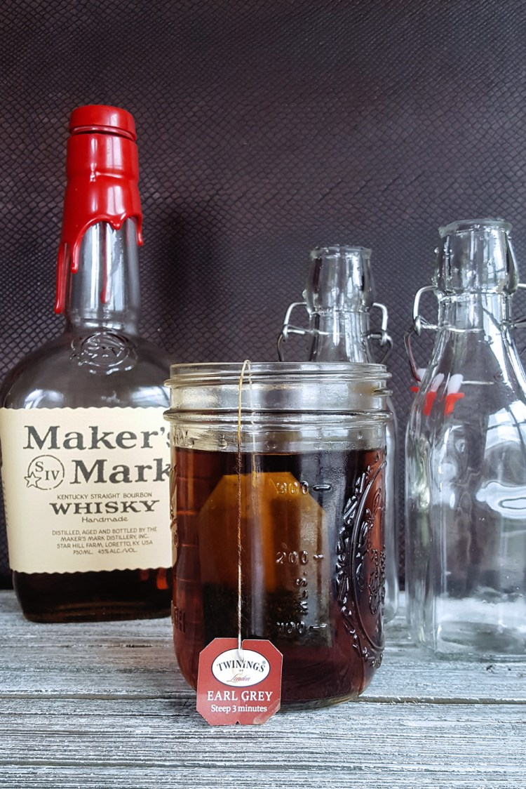 A bottle of whisky and two swing-top bottles in the background with a jar of bourbon being infused with tea in the foreground.