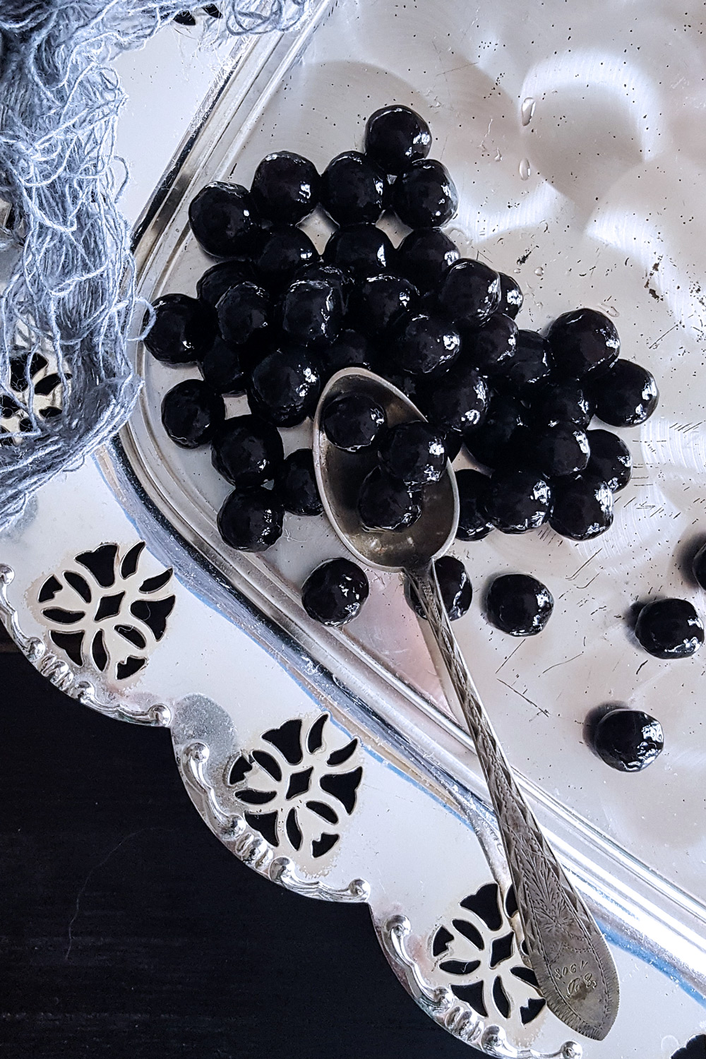 "A pile of black tapioca pearl ""caviar"" with a silver spoon."