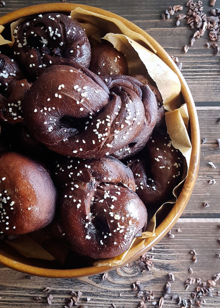 Wooden bowl of dark ale and bitter chocolate pretzel knots on a wooden background.