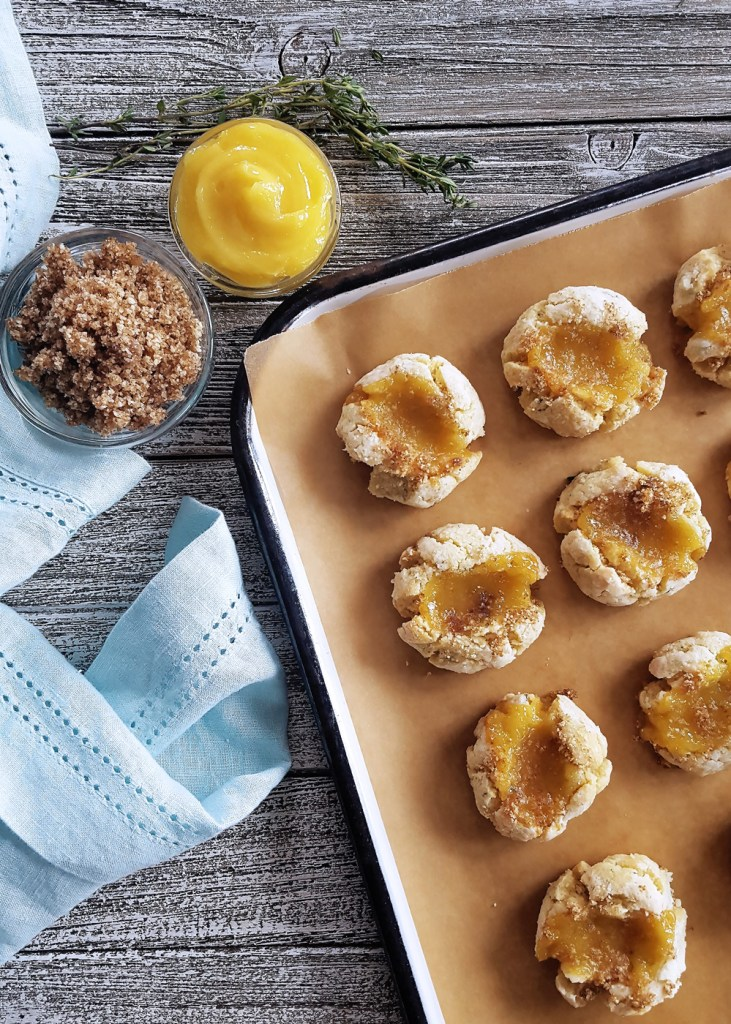 An overhead view of a white enamel tray full of thyme thumbprint cookies, with lemon curd and crumble on the side. | FeastInThyme.com