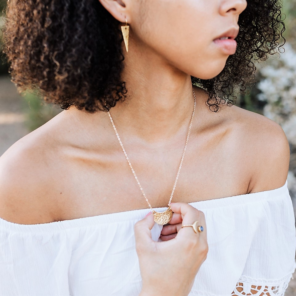 A model showcasing earrings, a necklace, and a ring by Nine Birds Studio.