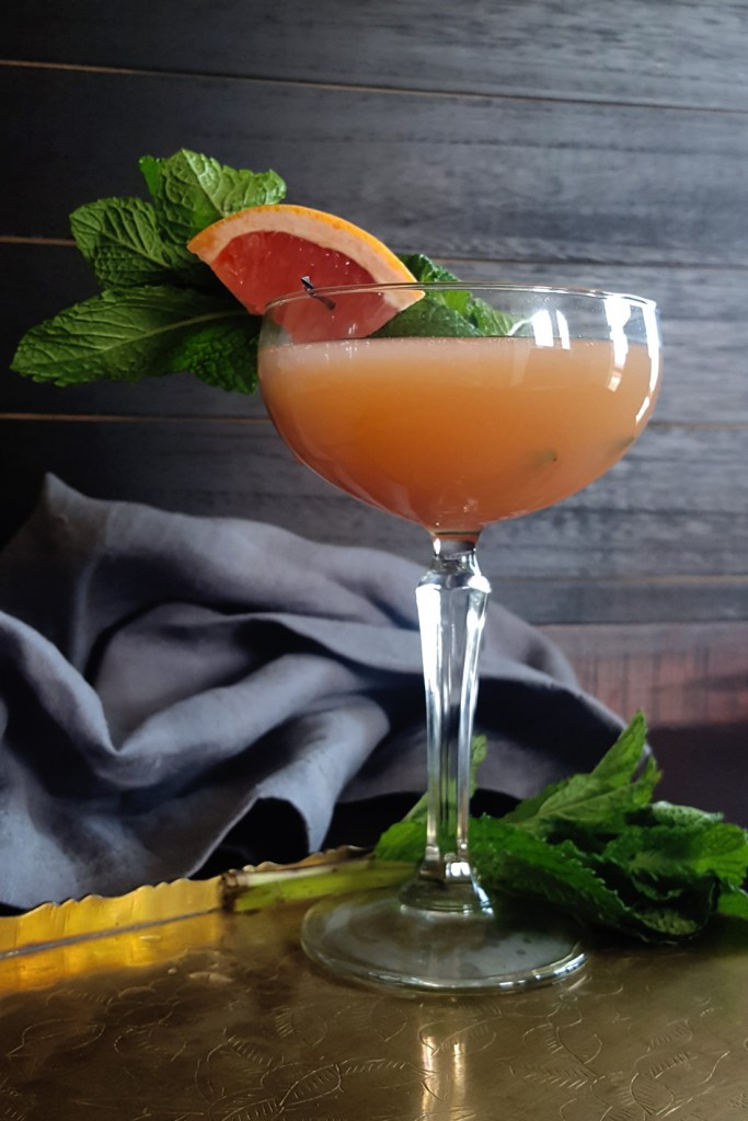 Close-up of a coupe glass filled with a bourbon grapefruit cocktail, garnished with mint leaves and a slice of grapefruit.