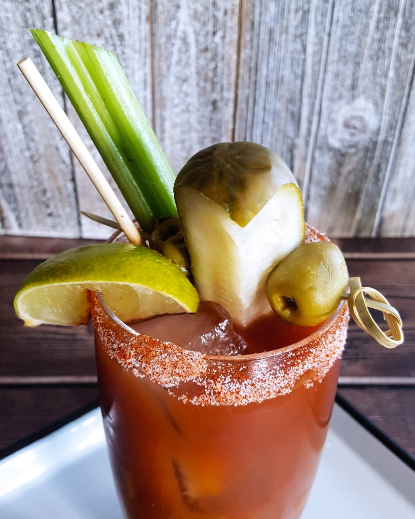 Close-up image of the Bloody Mary garnishes: lime, pickle, olives, celery.