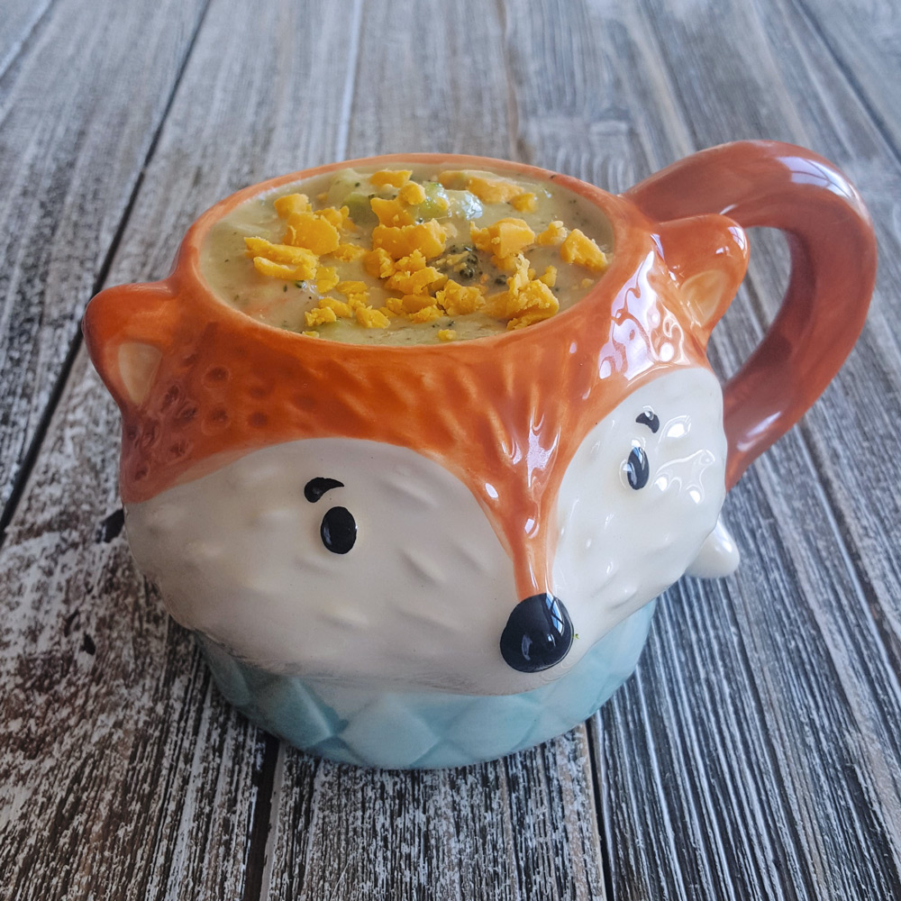 A fox-shaped mug full of broccoli and cheese soup.