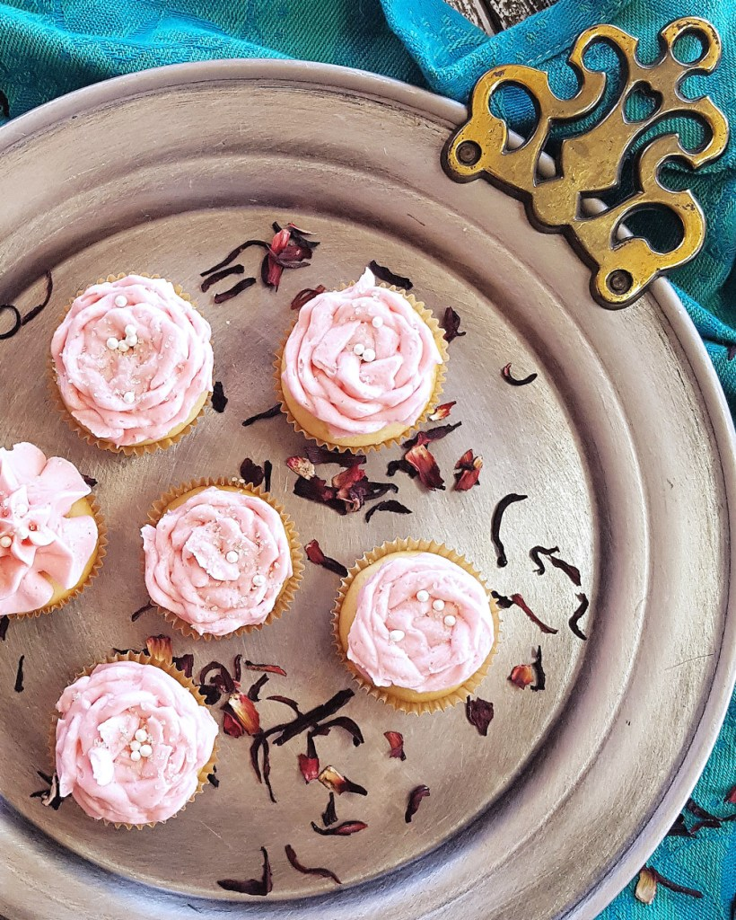 A few tiny cupcakes frosted with pink icing on a silver plate, surrounding by dry hibiscus flowers.
