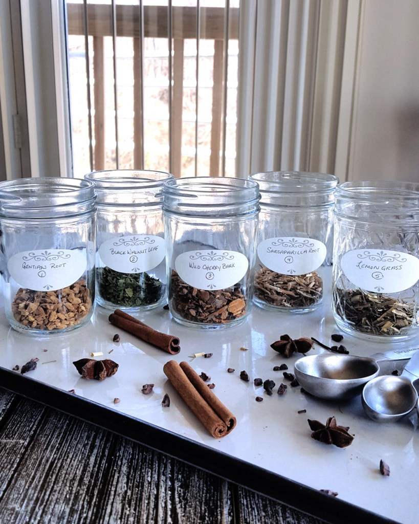 Five half-pint jars filled with botanicals ready to be infused with liquor.