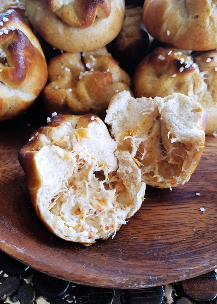 A close-up of a single torn open cran rangoon pretzel bun, showing the creamy crab filling.