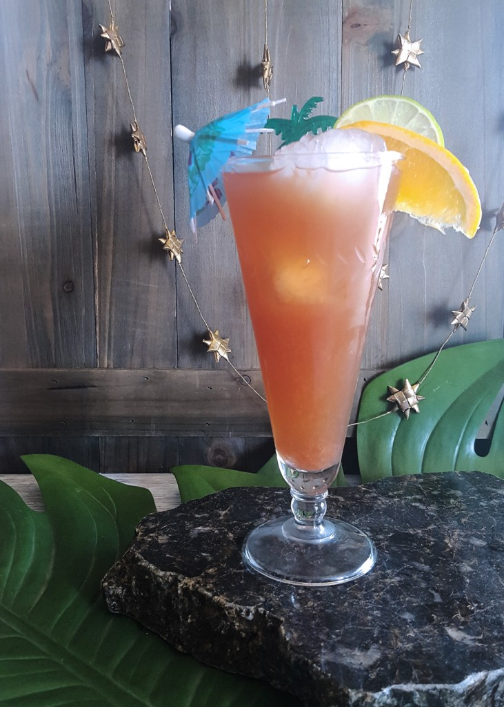 A tall glass of pinkish orange liquid filled with ice and topped with a blue umbrella and citrus garnishes.