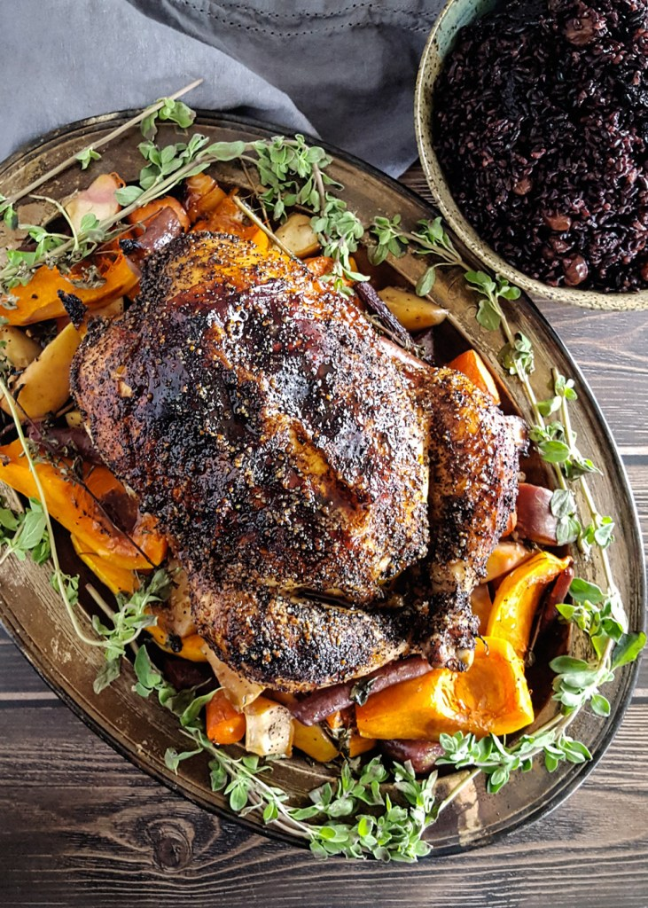 A well-seasoned roast chicken on a bed of butternut squash and carrots surrounded by fresh marjoram.