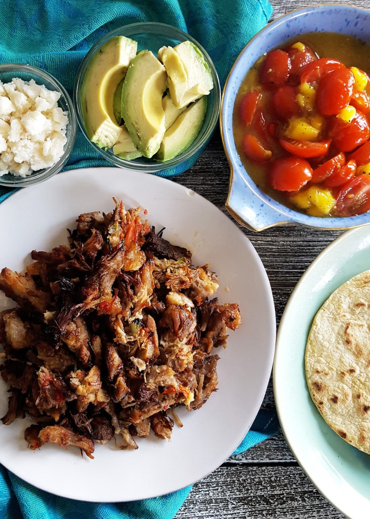 Overhead view of pulled pork, tomato mango salsa, and slices of avocado.