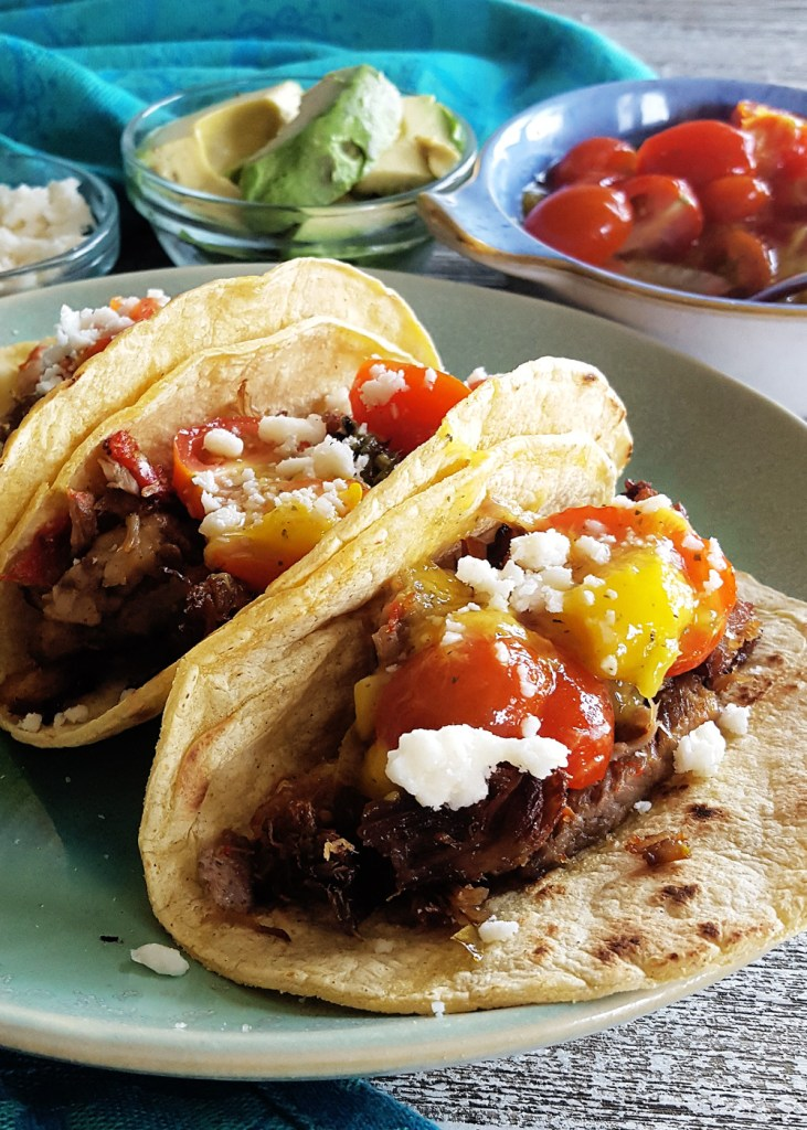 Close-up of pulled prok tacos with tomato mango salsa and cotija cheese crumbles.
