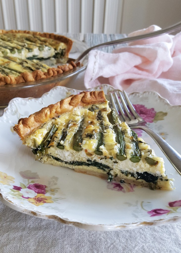 A single slice of asparagus goat cheese quiche cut so that you can see the layers of spinach, egg, and asparagus spears on top.
