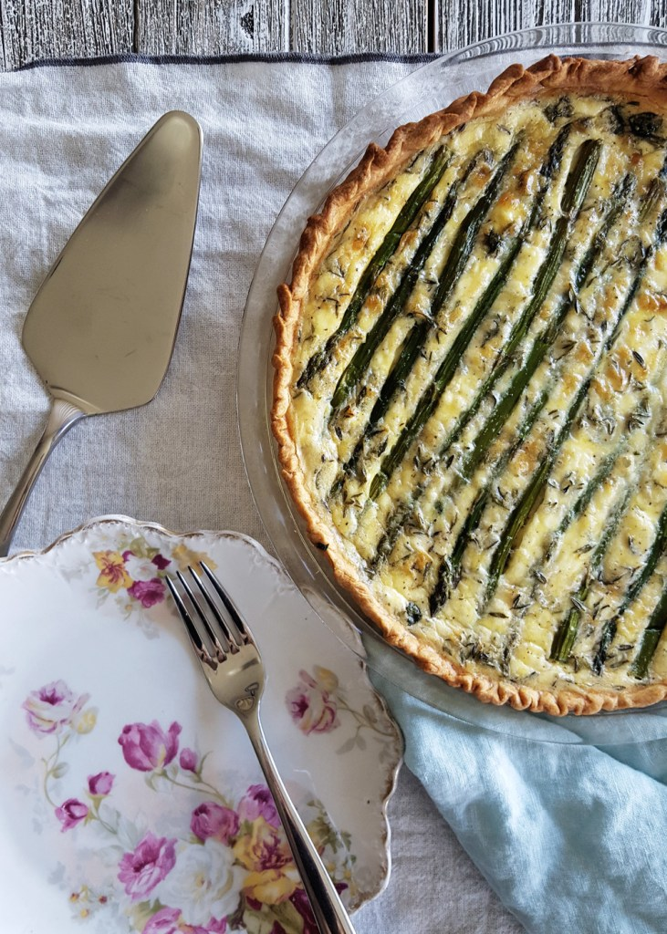 An asparagus goat quiche with a plate, fork, and serving utensil.