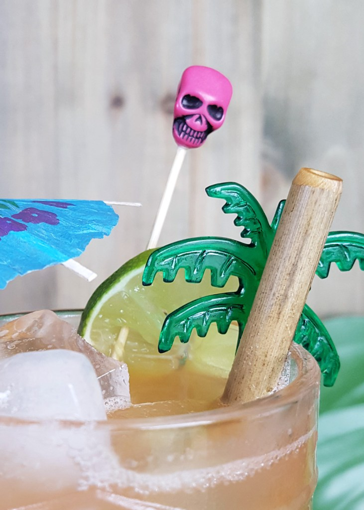 Close-up of the pink skull and green palm tree swizzle stick in a glass of Zombie Punch.
