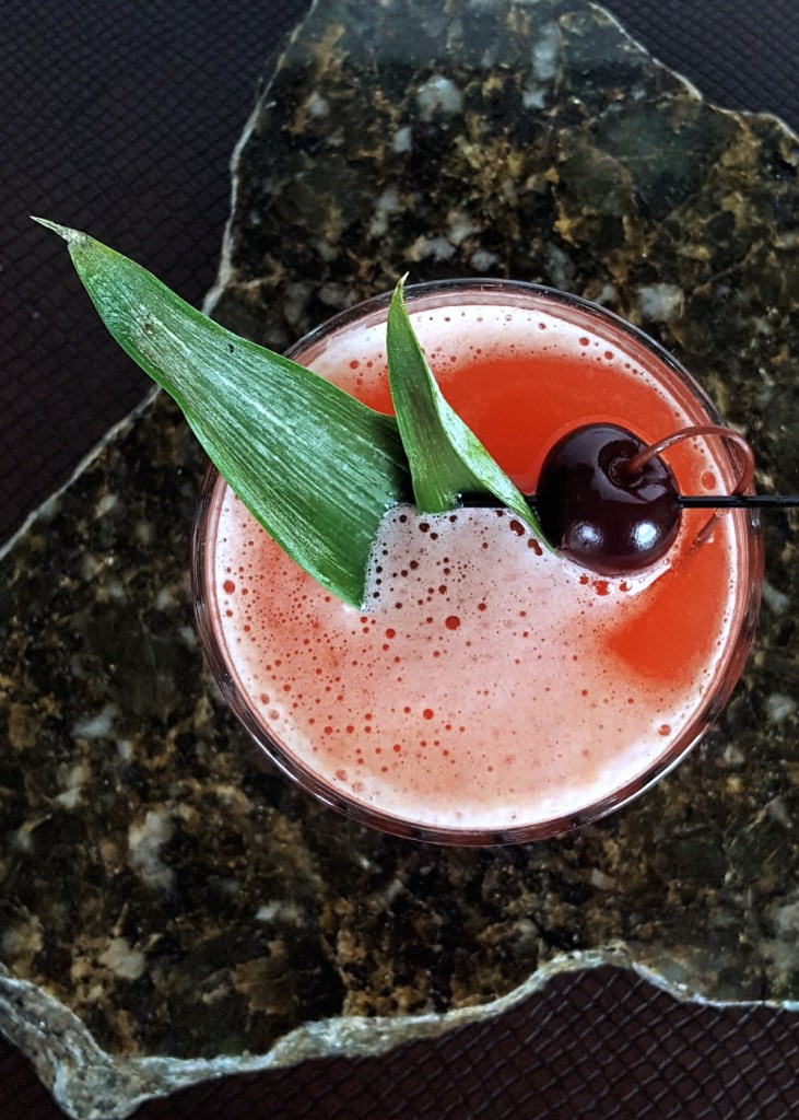 Overhead shot of a pinkish-red passion fruit cocktail with two pineapple leaves and a cocktail cherry.