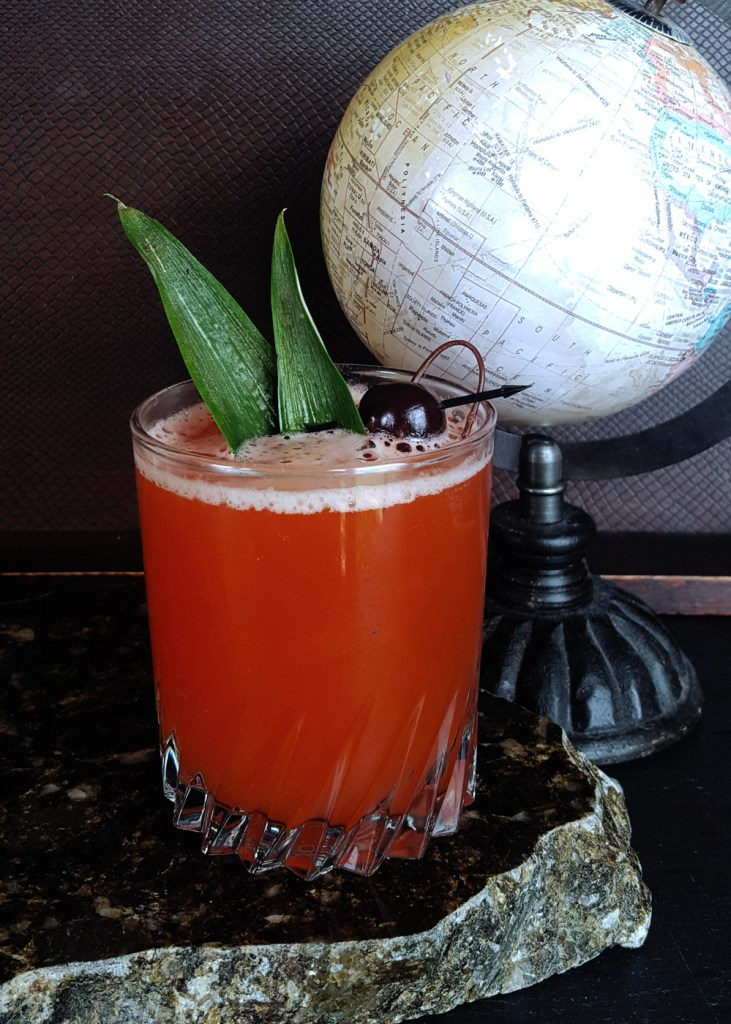 A passion fruit rum cocktail with a dark background and model globe.