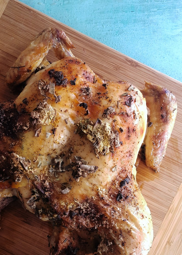 A whole roasted spatchcocked chicken on a cutting board.