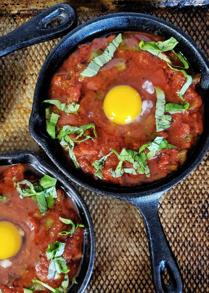 Two skillets filled wit tomato sauce and topped with raw egg before baking.