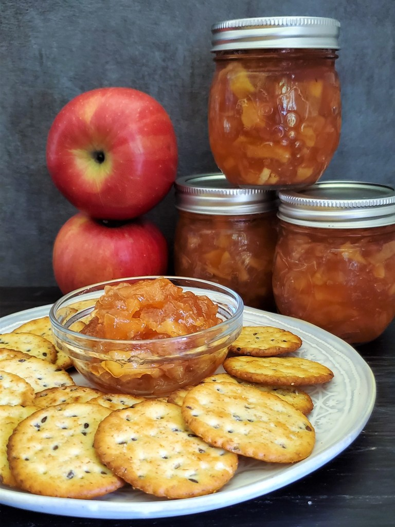 A small bowl of apple jam surrounded by crackers, with a stack of three jars and two apples behind.