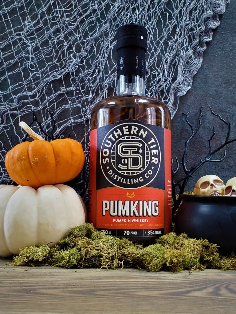 A bottle of Southern Tier Pumking Whiskey flanked by stacked pumpkings and a little cauldron of skulls.