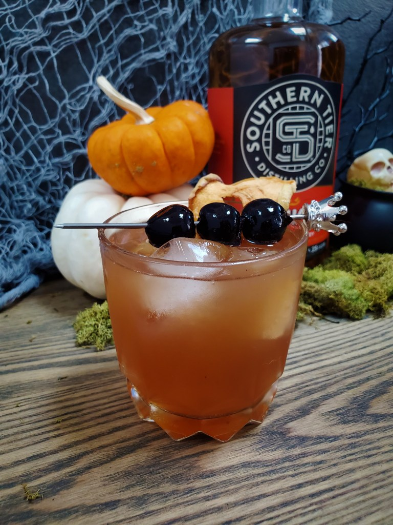 The Royal Orchard Cocktail in a rocks glass with a crown-topped cocktail pick lined with dark cherries with bottle of Southern Tier Pumking Whiskey behind.