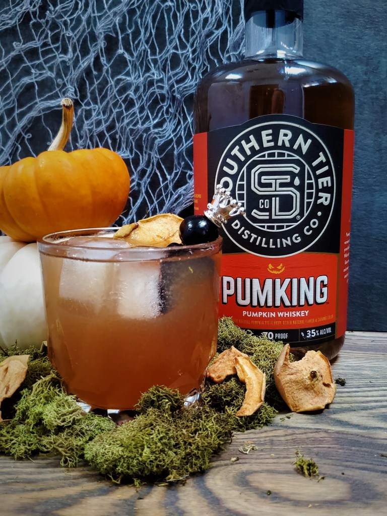 A glass of The Royal Orchard next to a bottle of Pumking Whiskey.
