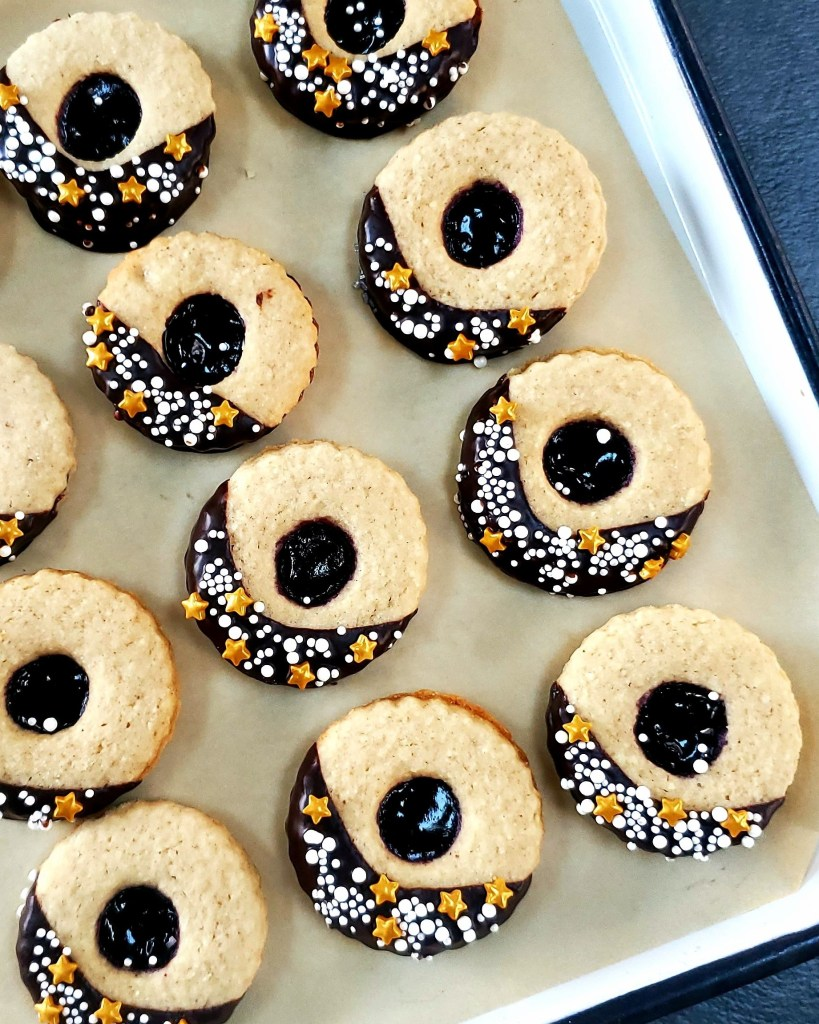 Chocolate and sprinkle dipped linzer tarts lined up on a white enamel baking tray.
