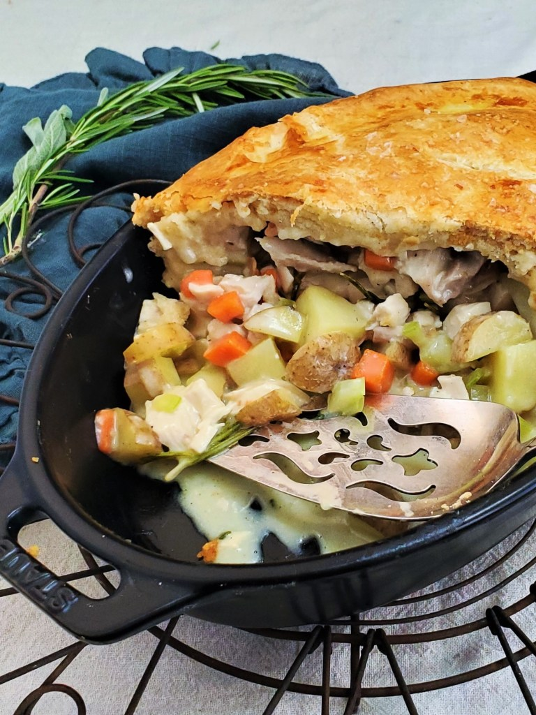 Golden chicken pot pie and silver pie server, cut open to reveal creamy chicken filling.