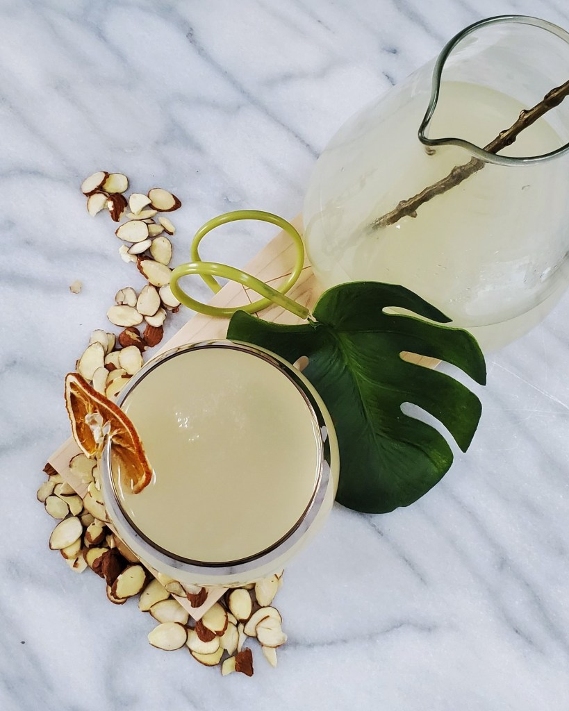 Overhead image of a candied almond lemon drop cocktail along with pitcher on a marble slab.