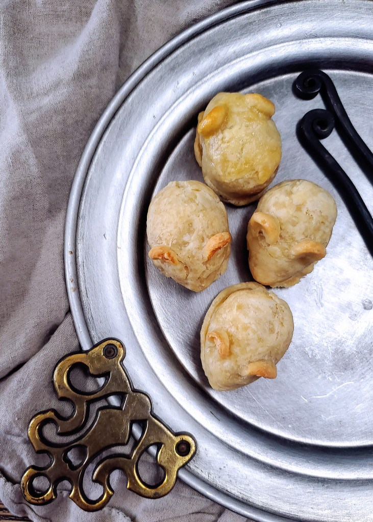 Four pastry mice hand pies on a pewter platter from above.