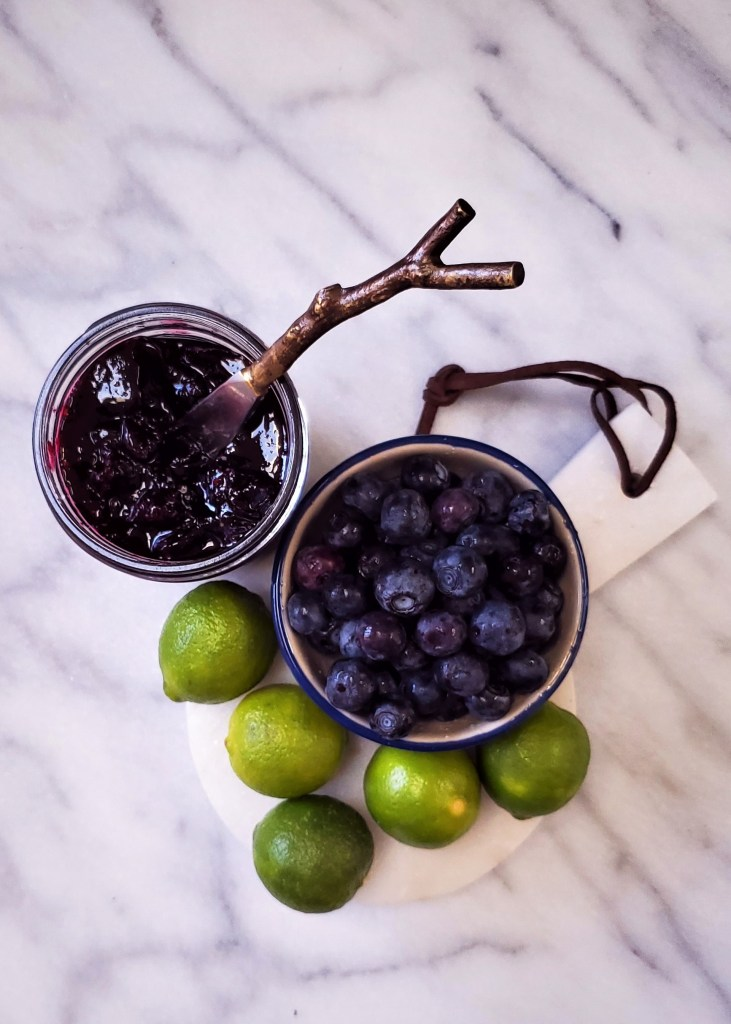 An open jar of key lime blueberry jam, alongside a bowl of blueberries and a pile of key limes