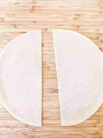 Cut tortilla into half for Potato Samosa recipe.