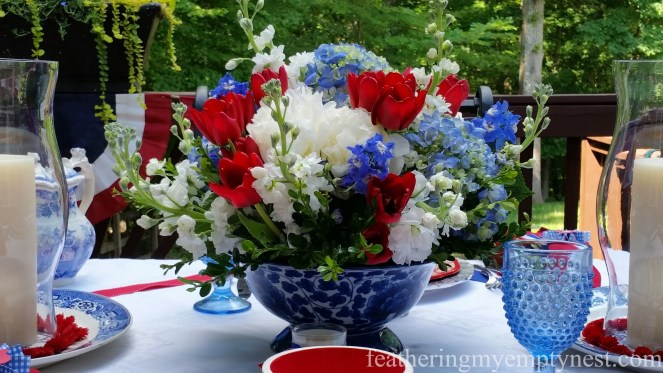 Red tulips, white peonies and stock, and blue hydrangeas and delphiniums make up floral arrangement on Old Fashioned 4th of July Tablescape