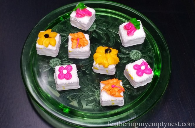 Flower decorated petit fours displayed on a vintage pressed glass cake plate on Romantic Flower-themed Summer Tablescape