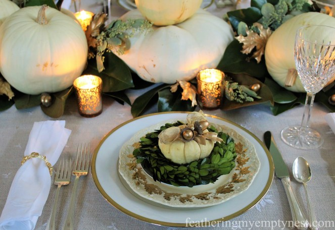Gold rimmed plates topped with mini boxwood wreath and baby boo pumpkins embellished with gold ribbon and acorns --A Nature-Inspired Elegant Thanksgiving Tablescape