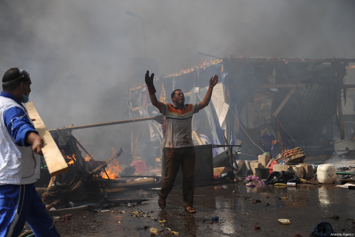 A file photo dated August 14 2013 shows an Egyptian man in despair as Egyptian security forces stormed the Rabaa Adawiyya sit-in in Cairo, killing 1,000 people [Mohammed Elshamy/Anadolu Agency]
