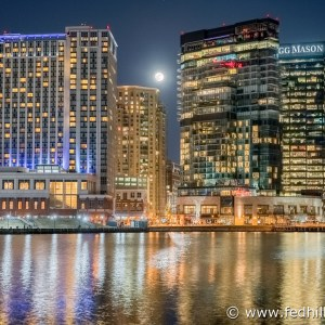 Fine art photo of moonrise over Harbor East hotel and office buildings reflected in water in Baltimore City, Maryland.