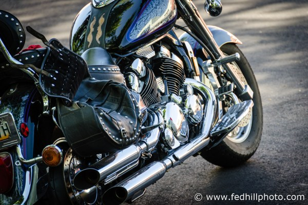 Fine art photograph of afternoon sunlight on a shiny motorcycle engine, exhaust, seat, gas tank, and wheels.