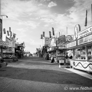 Fine art black and white photograph of the empty midway on a morning at the Maryland State Fair. Vendors selling french fries, funnel cake, and games.