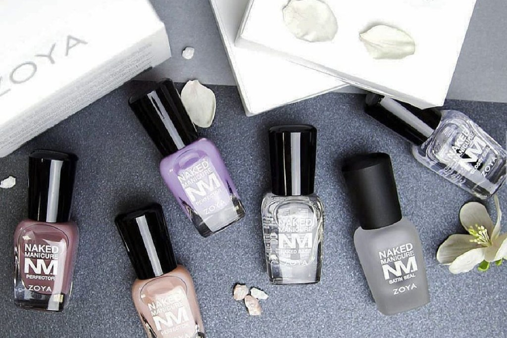 ZOYA Naked Manicure Perfectors and base coats are scattered on a gray surface with flower petals surrounding and a white ZOYA box in the left corner.