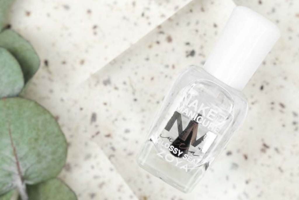 ZOYA Ultra Glossy Seal top coat is laying on a textured background next to plant leaves.